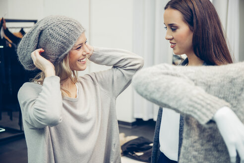 Young woman assisted by friend putting on woolly hat in a boutique - CHAF001349