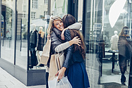 Two happy young women with shopping bags hugging outside a store - CHAF001354