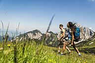 Austria, Tyrol, Tannheimer Tal, young couple hiking on alpine meadow - UUF005050