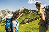 Austria, Tyrol, Tannheimer Tal, young couple hiking on alpine meadow - UUF005059