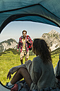 Austria, Tyrol, Tannheimer Tal, young couple camping on alpine meadow - UUF005061