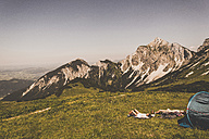 Austria, Tyrol, Tannheimer Tal, young couple resting next to tent on alpine meadow - UUF005065