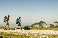 Austria, Tyrol, Tannheimer Tal, young couple hiking on mountain trail - UUF005087