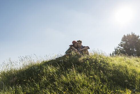 Austria, Tyrol, Tannheimer Tal, young couple hugging on alpine meadow - UUF005098