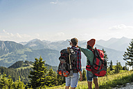 Austria, Tyrol, Tannheimer Tal, young couple in alpine landscape looking at view - UUF005106