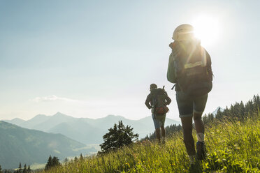 Austria, Tyrol, Tannheimer Tal, young couple hiking on alpine meadow in backlight - UUF005107