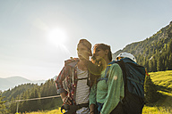 Austria, Tyrol, Tannheimer Tal, young couple in alpine landscape looking at view - UUF005108