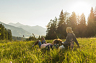 Austria, Tyrol, Tannheimer Tal, young couple resting on alpine meadow - UUF005114