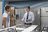 Shop assistant talking to young couple shopping kitchen equipment - ZEF007057
