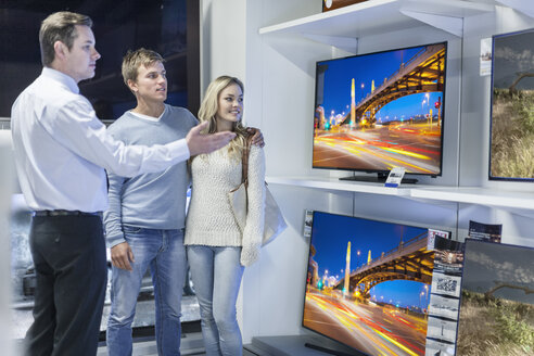 Shop assistant showing flatscreen TVs to young couple - ZEF007473