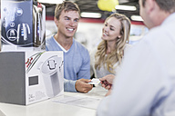 Young couple at counter in shop paying for purchase - ZEF007353