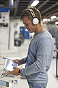 Young woman with headphones testing digital tablet in a shop - ZEF007361