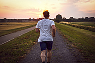Rear view of man jogging at sunset - PUF000391