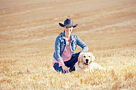 Portrait of young woman sitting with Golden Retriever on a stubble field - MAEF010819