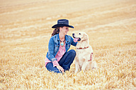 Young woman and Golden Retriever sitting on a stubble field - MAEF010823