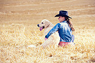Young woman and Golden Retriever sitting on a stubble field - MAEF010826