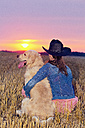 Young woman with Golden Retriever sitting on stubble field at twilight - MAEF010832