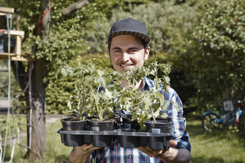 Man in garden holding tray with seedlings - RHF000983