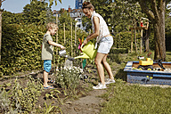 Mother and son watering flowers in garden - RHF001031
