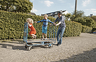 Father pushing handcart with two children in allotment-garden area - RHF001033