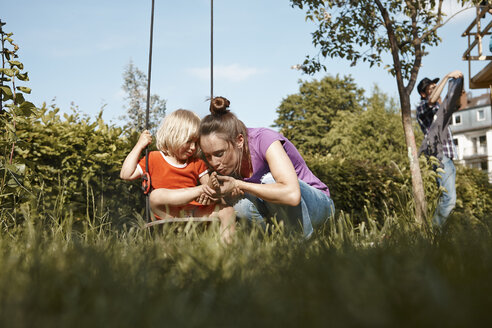 Mother caring for injured daughter in garden - RHF001008