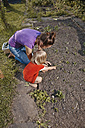 Mother and daughter planting seedlings in garden - RHF001018