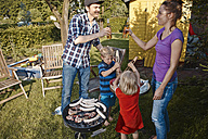 Family having a barbecue in garden - RHF001021