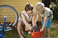Mother and son repairing bicycle together - RHF001028