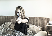 Woman sitting in her bed pointing a pistol at viewer - FC000711