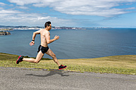 Shirtless man jogging at the coast - MGOF000368