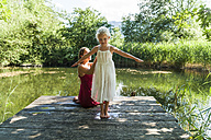 Girl with mother on jetty at a lake - TCF004783