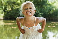 Portrait of blond girl with wet dress at a lake - TCF004785