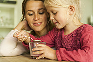 Mother looking at daughter with glass and spoon - TCF004795