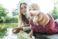 Girl lying with mother on jetty at a lake pointing finger - TCF004802
