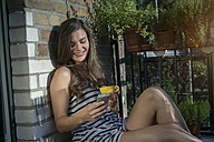 Young woman on balcony drinking morning coffee, holding smart phone - RIBF000237