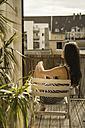 Germany, Young woman sunbathing on balcony - RIBF000167