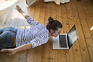 Young woman at home lying on wooden floor with laptop, pretending to fly - RIBF000182