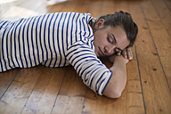 Young woman at home lying on wooden floor, eyes closed - RIBF000184