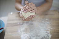 Young woman preparing pizza dough in kitchen - RIBF000187