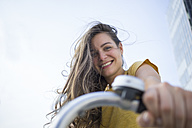 Portrait of smiling young woman holding handlebar of her bicycle - RIBF000217