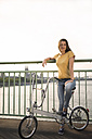 Germany, Cologne, young woman with bicycle standing on Rhine bridge - RIBF000222