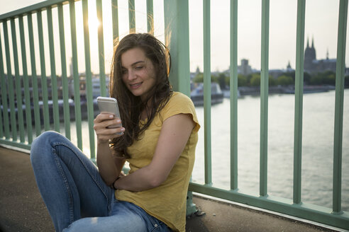 Germany, Cologne, young woman sitting on Rhine bridge looking at her smartphone - RIBF000235