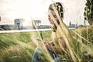 Germany, Cologne, woman with beer bottle and smartphone relaxing on a meadow near Rhine River - RIBF000225