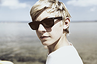 Germany, Niendorf, young boy with sunglasses turning his head back, close up - MEMF000904