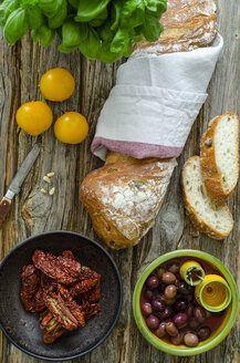 Olive bread, basil, dried and fresh tomatoes, black olives and a knife - ODF001172