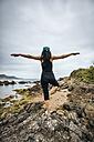 Spain, Asturias, Gijon, woman doing yoga on a rocky beach - MGOF000389