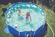 Boy and girl in swimming pool surrounded by balloons - SARF002066