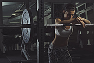 Muscular athlete leaning on barbell in gym - MADF000459