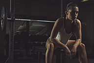 Female athlete sitting on bench, contemplating - MADF000469