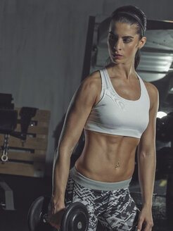Portrait of a female athlete training with dumbbells in gym - MADF000484